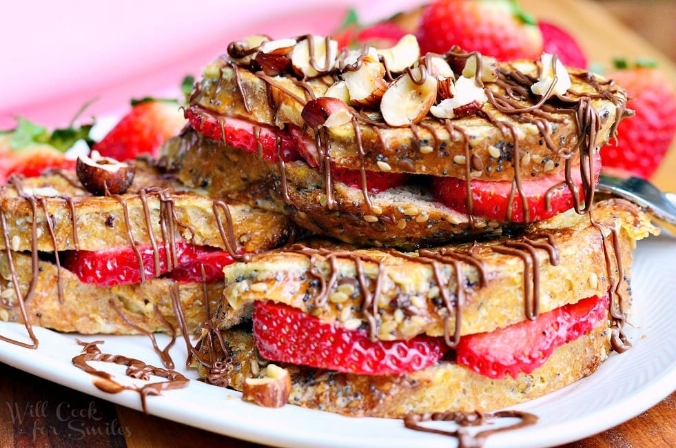 horizonal photo of Fruit Filled Hazelnut French Toast with strawberries stacked up on a white plate