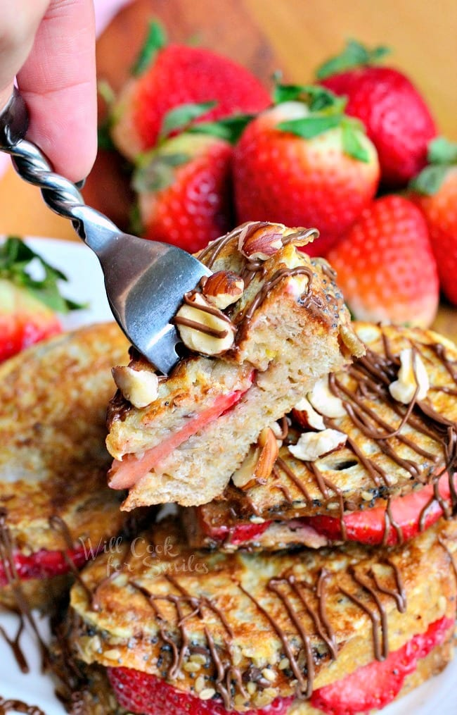 Fruit Filled Hazelnut French Toast with strawberries stacked up on a white plate with a fork lifting up a bite