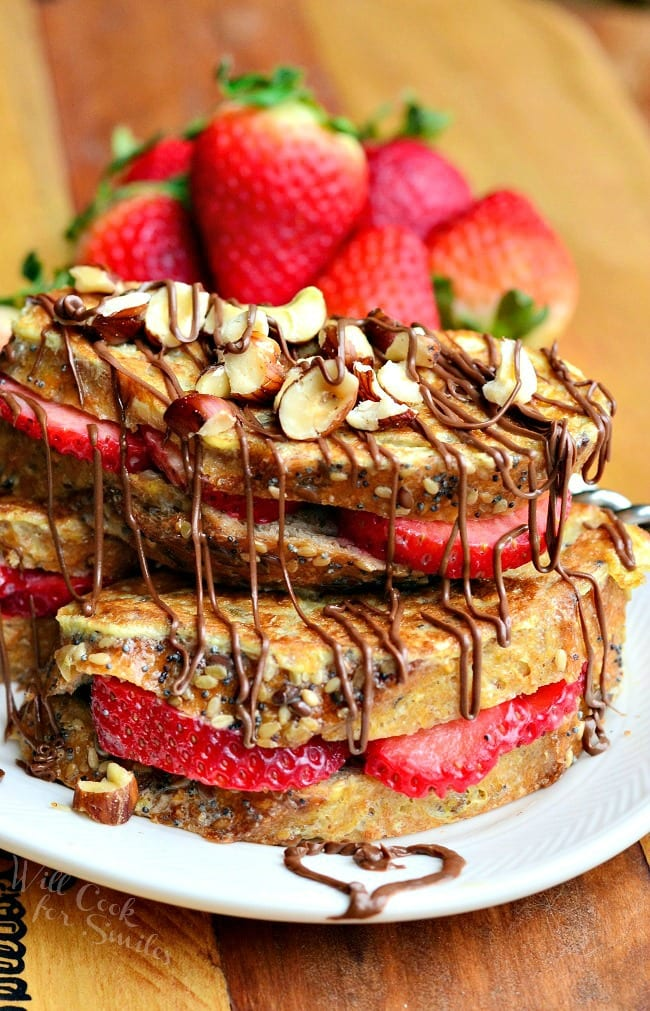 Fruit Filled Hazelnut French Toast with strawberries stacked up on a white plate
