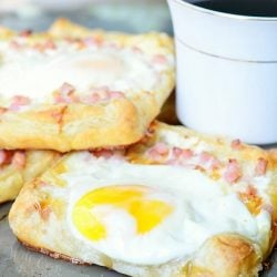 shignled pile of Ham egg cheese breakfast pastry and a cup of coffee on a sheet try and table