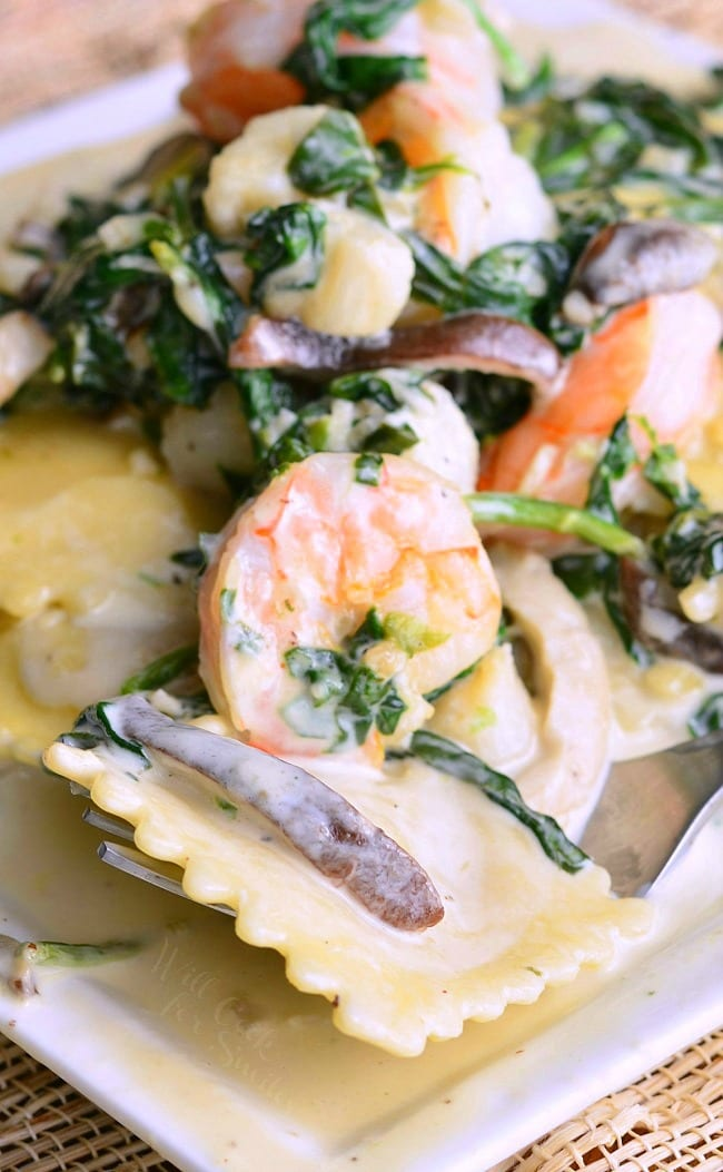 Ravioli with Seafood, Spinach & Mushrooms on a white plate