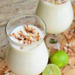2 dessert beverage glasses filled with creamy tropical smoothie on a wooden cutting board for presentation and toasted coconut flakes and sliced limes scattered around the base of the glasses.