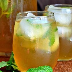 2 glasses of brewed honey mint green iced tea on a wooden table with mint laying on the table to the left of the glasses and a pitcher filled with more tea in the background to the left of glasses.