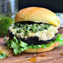 front view of Italian stuffed portabello burger on a bun and bed of lettuce sitting on a wooden board with a spoon of pesto at the bottom left and block of cheese in the background along with a bottle of pesto