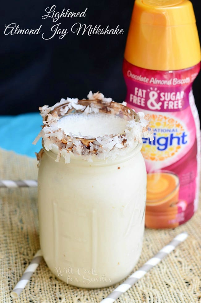 Milkshake in a jar with coconut around the rim and creamer in the background