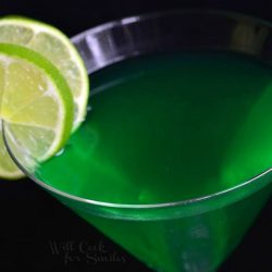 view from above of a martini glass filled with lime martini and garnished with lime garnishes