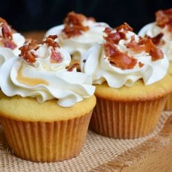 close up view of 4 maple bacon cupcakes on a burlap cloth on wooden table with a black background