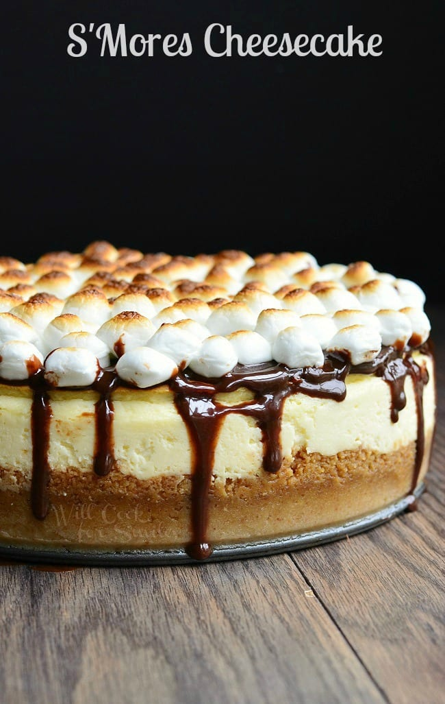 S'Mores Cheesecake with mini marshmallows on top with chocolate sauce over it