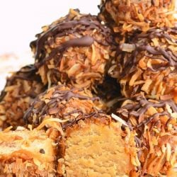 several Samoas cookie truffles on a white plate with toasted coconut flakes laying in the foreground