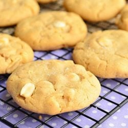Sweet and salty white chocolate chip peanut butter cookies on a cooling rack on top of blue cloth