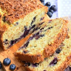 loaf of toasted coconut blueberry bread with the first 3 slices stacked in front of the rest of the loaf on a wooden cutting board with blueberries scattered around on table.
