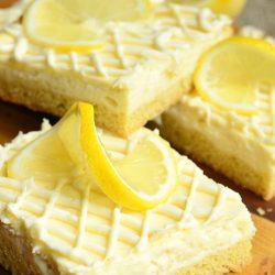 4 Vanilla bean lemon cheesecake bars on a wooden cutting board topped with sliced lemons