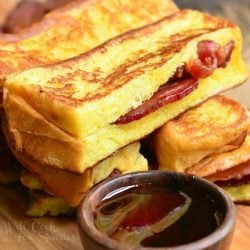 Cut bacon stuffed brioche french toast sticks stacked on a wooden cutting board with a small bowl of syrup