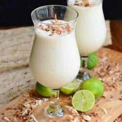 2 dessert glasses filled with creamy tropical smoothie on a wooden cutting board with coconut chavings around base of glasses along with cut limes