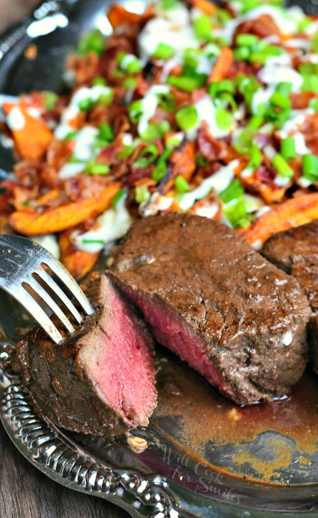 Ribeye Filet and Loaded Sweet Potato Wedges on  a plate a fork taking a piece of the streak