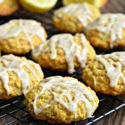 Glazed cookies on a cooling rack on a wooden table with halved lemons in between cookies