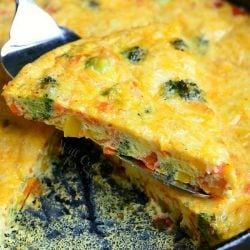 Fork lifting up one portion of vegetable and cheese overload breakfast bake over rest of dish
