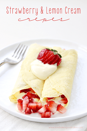 crepes with strawberries and a lemon cream inside of them with a strawberry and whipped cream on top on a white plate with a fork to the left