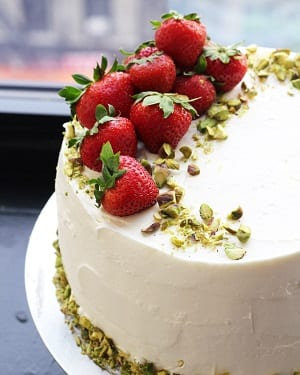 strawberry cake with white frosting and pistachios and strawberries on top