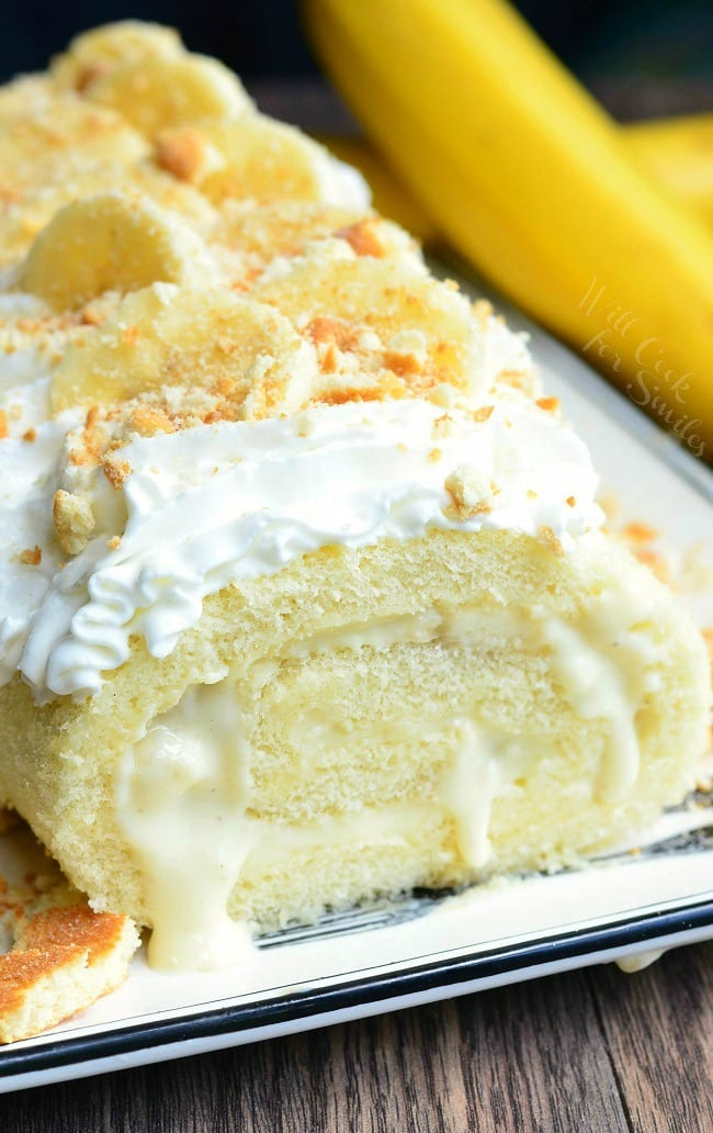 Banana Pudding Cake Roll on a plate with whipped cream, crushed vanilla waffers and banana on top with a unpeeled banana to the right
