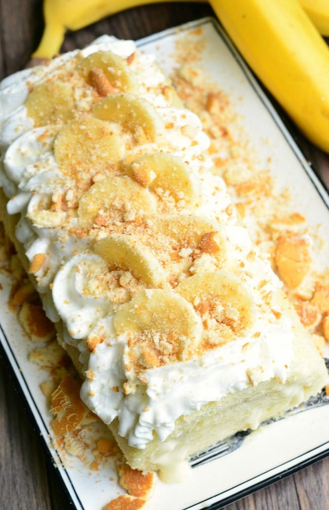 top view photo of Banana Pudding Cake Roll on a plate with whipped cream, crushed vanilla waffers and banana on top with a unpeeled banana to the right