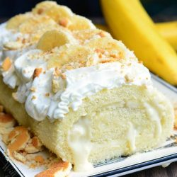 banana pudding cake roll on a decorative white rectangular plate on a wooden table with 2 bananas in the background