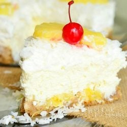 1 slice of pina colada cheesecake in front of the rest of the cake on a tan burlap style placemat
