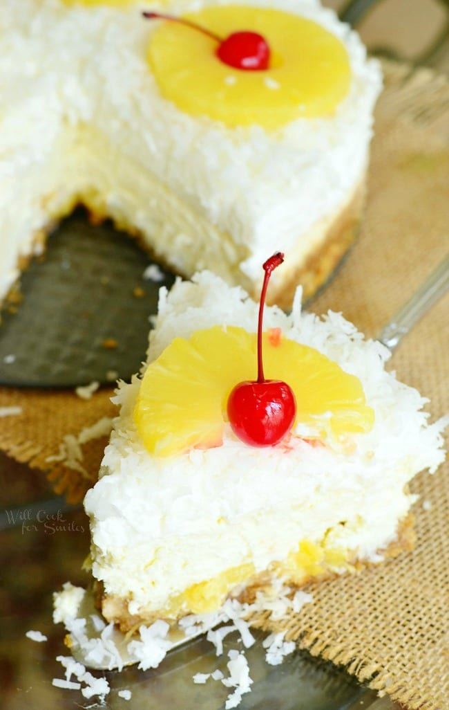 Top view of pina Colada Cheesecake with coconut, cherry, and pineapple