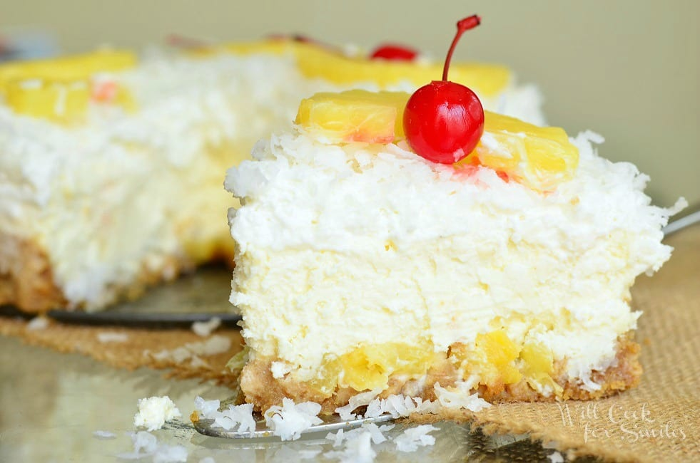Pina Colada Cheesecake slice on table with coconut, cherry, and pineapple on top