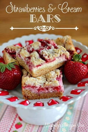strawberry bars on a cake platter with strawberries around it