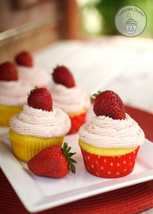 strawberry lemon cupcakes with strawberry frosting and a cherry on top on a white plate