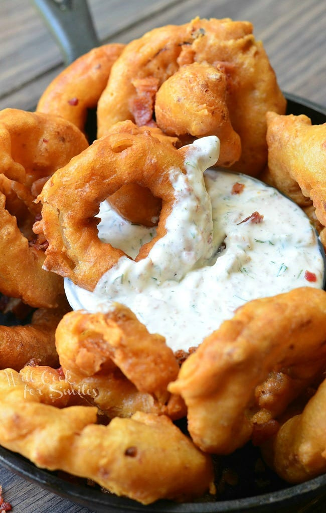 Bacon Onion Rings are served in a black skillet around a dish of Bacon Ranch Dipping Sauce, which is placed in the middle of the skillet. An onion ring that has been partially dipped into the sauce is laying on top of the dip.