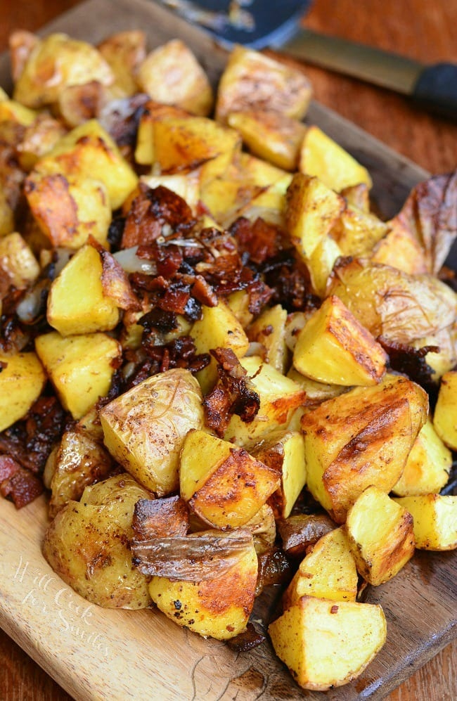 Brown Butter Roasted Potatoes with Bacon and Pearl Onions on a cutting board