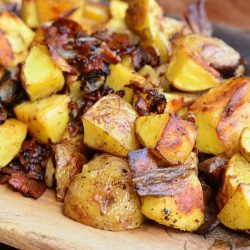 close up view of cutting boared covered with brown roasted potatoes