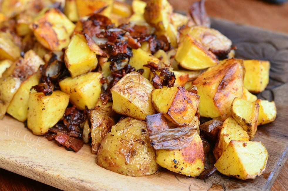 Roasted Potatoes with Bacon and Pearl Onions on a wood cutting board