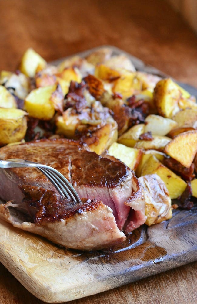 steak with a fork taking a piece and Roasted Potatoes with Bacon and Pearl Onions on a wood cutting board