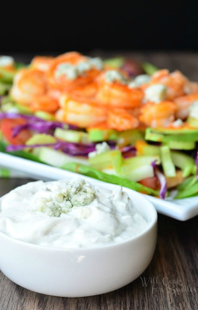 Homemade Blue Cheese Dressing is presented in a small, white bowl. It has blue cheese crumbles on top. In the background is the Buffalo Shrimp Salad.