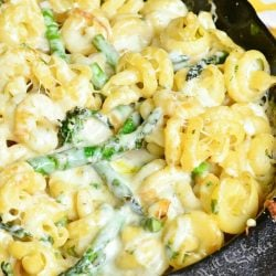 black skillet filled with extra cheesy lemon aspaus pasta on a white and yellow towel on a wooden table as seen from above