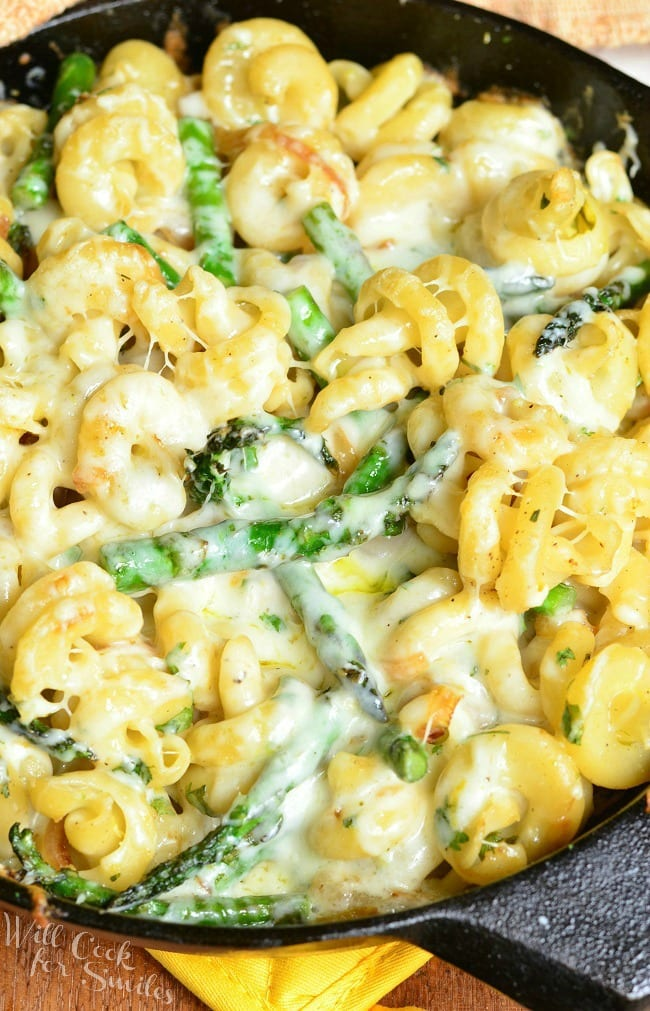 Top view of Extra Cheesy Lemon Asparagus Pasta Skillet in a black skillet. In the skillet, there are many noodles and asparagus covered in a creamy sauce.