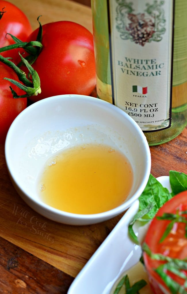 There is a white bowl with white balsamic reduction in it. It's yellow in color. There is a bottle of white balsamic vinegar and whole tomatoes in the background.
