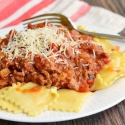 small round white plate with ravioli and meat sauce on a wooden table viewed close up
