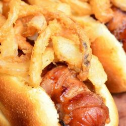 close up view of bbq bacon crsipy onion hot dogs on a wooden table