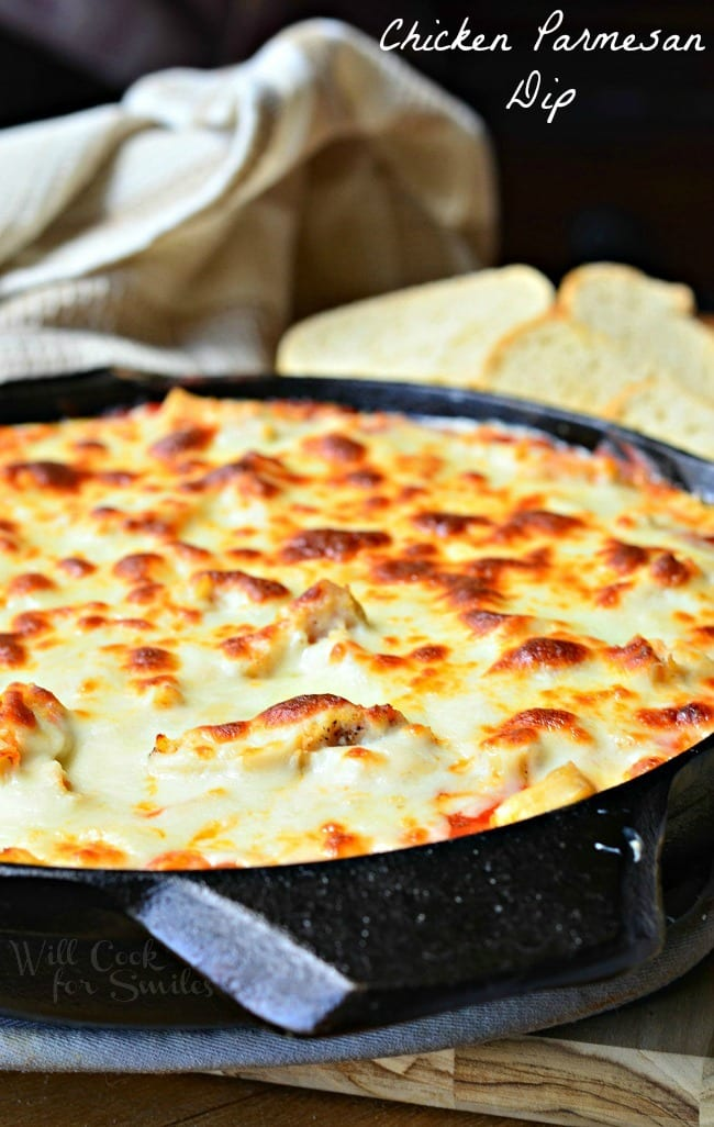 Chicken Parmesan Dip in a black skillet. The top is cheese that has been browned to perfection. Pieces of bread are in the background.