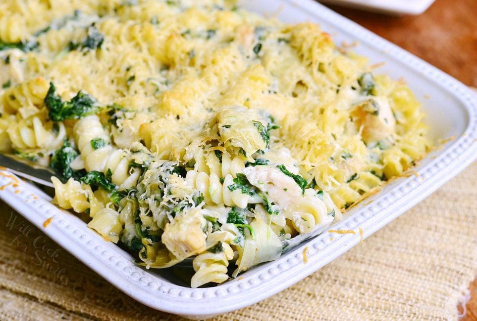 Chicken Spinach and Artichoke Pasta served in a white casserole dish.