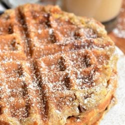 3 stacked cinnamon peach oat waffles on a white plate with a glass of coffe in the background