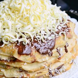Crepe Cake on a white plate covered with chocolate and white chocolate shavings