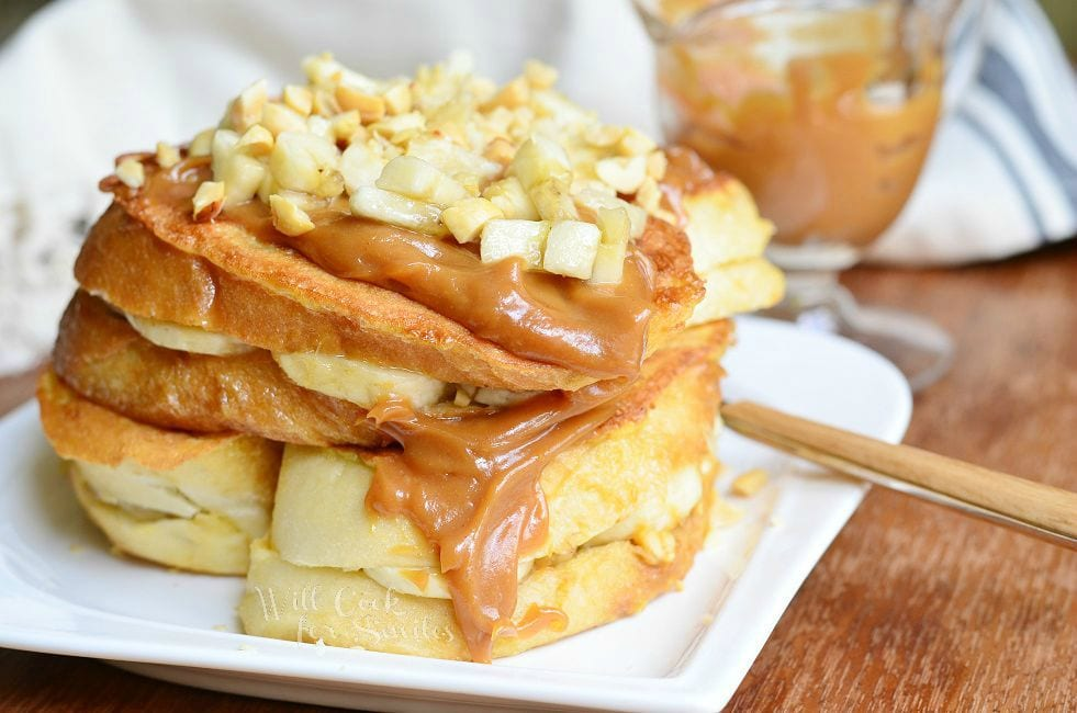 Stacked Peanut Butter Banana Stuffed French Toast served on a white dish. Peanut butter sauce is smothered on top and goes down the side. Chopped peanuts and banana pieces are also on top.