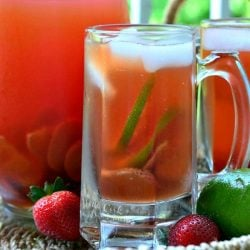 Clear glass beer mug filled with strawberry lime infused iced tea in front of another mug and pitcher filled with tea viewed close up