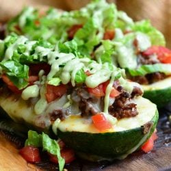 2 taco stuffed zucchini boats on a wooden board topped with avocado dressing viewed close up