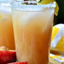 2 pint glasses filled with white peach margarita on a wooden serving tray wtih slice peaches in foreground